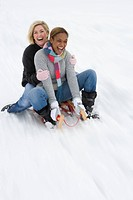 Women sledding down snow slope (thumbnail)