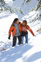 Mixed race couple walking in snow with sled