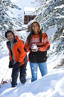 Mixed race couple playing in snow with snowball and sled