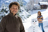 Portrait of mature man in winter setting, woman with snowman in background