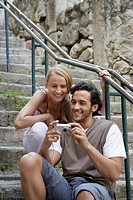 Young couple looking at digital camera