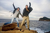 Couple jumping in a cliff by the sea