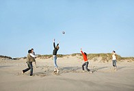 Five people playing with ball on beach