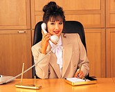 Businesswoman talking over phone while sitting in office