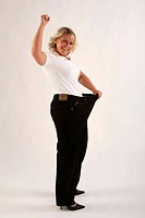 Woman with too big trousers after loosing weight, diet, cut out, winner pose