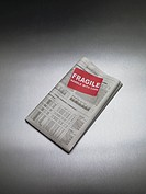 Fragile Sign on Newspaper Stock Listing