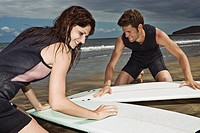 Couple Waxing Surfboards
