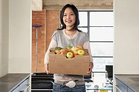 Young Woman Carrying Box of Fruits and Vegetables