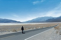 Rear view of businessman standing on lonely highway