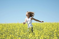 Girl Running Through Field of Canola