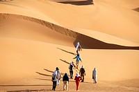 Tourists hike through sanddunes in the desert Mandara Libya