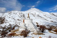 Tibetan Buddhism two white stupas on snow covered mountain Drak Yerpa Tibet China