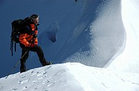 Mountaineer stands on snow covered ridge of Turgen Uul Kharkhiraa Mongolian Altai near Ulaangom Uvs Aymag Mongolia