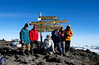 Successful group of mountaineers at the sign on the summit Uhuru Peak 5895 m crater rim Kilimanjaro Tanzania