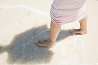 Young woman having a walk at the beach barefoot