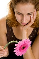 Young woman looking sadly on a gerbera
