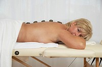Woman relaxing on massage bench with Hot Stones on the back