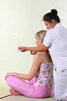 Young woman receiving a Thai massage (Nuad)