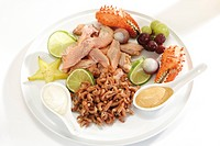 Fancy fish platter: smoked salmon filet, shrimps and crab pincers with fruits and dips