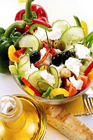 Colourful salad with capsicums, tomatoes, cucumber, olives and feta, with baguette