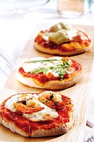Mini pizzas with mozzarella, prawn, rucola and artichokes