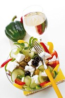 Fresh feta salad and a glass of white wine: Greek feta cheese, black and green olives, colourful capsicum stripes, cucumber and tomato wedges