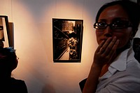 Young woman in an art gallery exhibiting photography, Shanghai, China