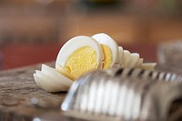 Sliced boiled egg beside egg slicer