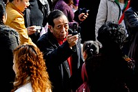 Elderly Chinese man taking photo with mobile phone in the crowd, Shanghai, China