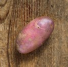 A purple potato on a wooden background