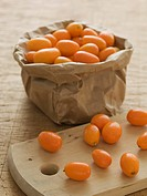 Kumquats in a sack and on a wooden board