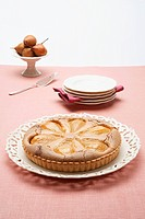 A pear tart on a cake plate