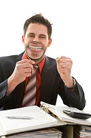 Young businessman sitting as his desk, cheering, holding a magnifying glass to his mouth, grinning
