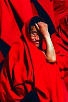 Tibetan lama in red Buddhist robe looking at camera, Shangri_la County, DiQing Tibetan Autonomous Prefecture, Yunnan Province, China