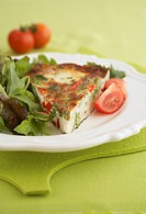 A piece of vegetable frittata with salad leaves