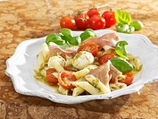Pasta salad with mozzarella, tomatoes, pesto and Parma ham