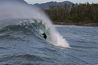 Surfer riding wave on the West Coast of Vancouver Island, British Columbia, Canada