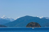 View eastward from Cortes Island to Coast Range mountains with small fishing boat in the distance, British Columbia, Canada