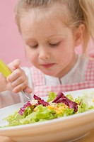 Little girl eating salad leaves with sweetcorn