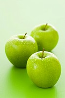 Three Granny Smith apples with drops of water