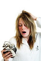 Girl holding an alarm clock, yawning