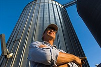 Agriculture _ Low angle view of a farmer inspecting his farming operation with a grain elevator in the background / near Hoffman, Minnesota, USA