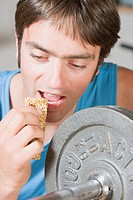 Man eating muesli bar on weight bench