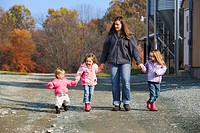 Agriculture _ A farm woman walks with her three young daughters along a gravel road next to poultry houses on their farm / near Buck, Pennsylvania, US...