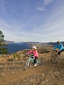 A mother and daughter mountain biking over Kamloops Lake, west of Kamloops, British Columbia, Canada