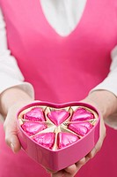 Woman holding box of heart_shaped chocolates