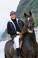 Man riding horse on beach, portrait