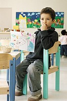 Boy holding up drawing in class room