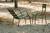 France, Paris, metal chairs set face to face in park