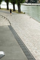 France, Paris, Canal Saint-Martin, person jogging along water's edge